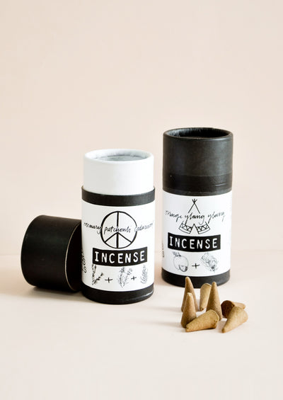 Two black cylinder cartons with white label and black text. Pile of brown cone shaped incense on the right side.