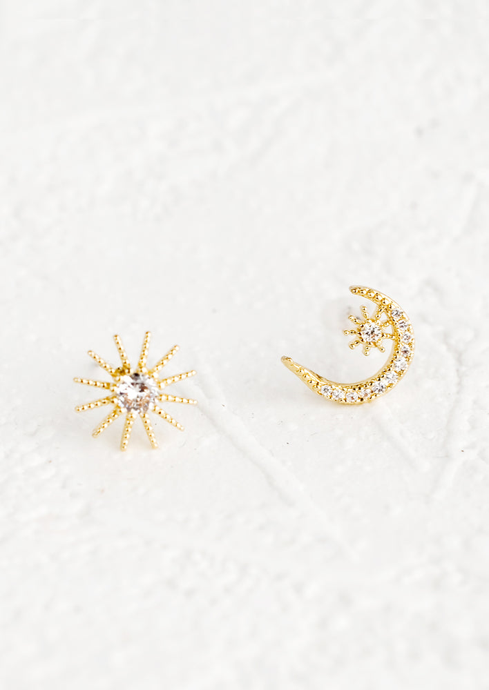 1: A pair of mismatched stud earrings, one piece is a sun and one piece is a moon.