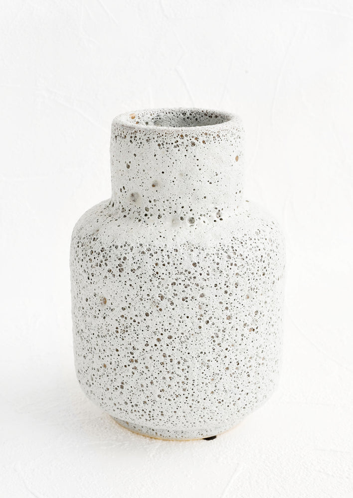 1: A ceramic vase in a heavily textured, crater-like light grey glaze with tapered opening.