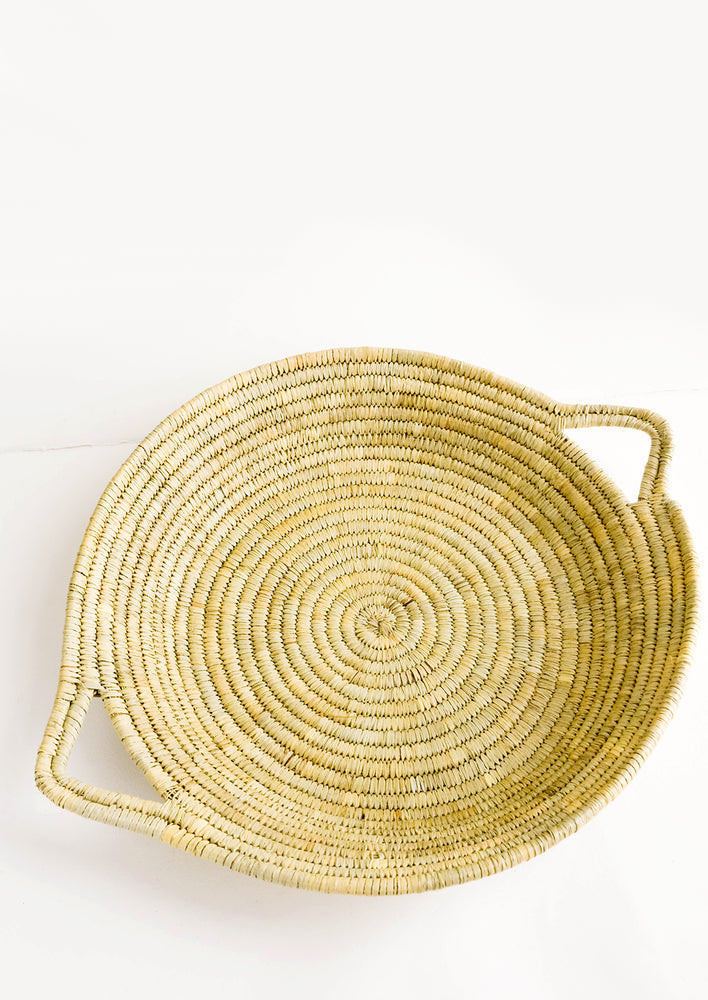 1: Flat, round platter woven from natural straw with handles at sides