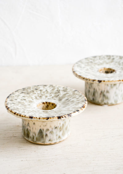 Short ceramic taper candle holders with saucer-like top in speckled reactive glaze