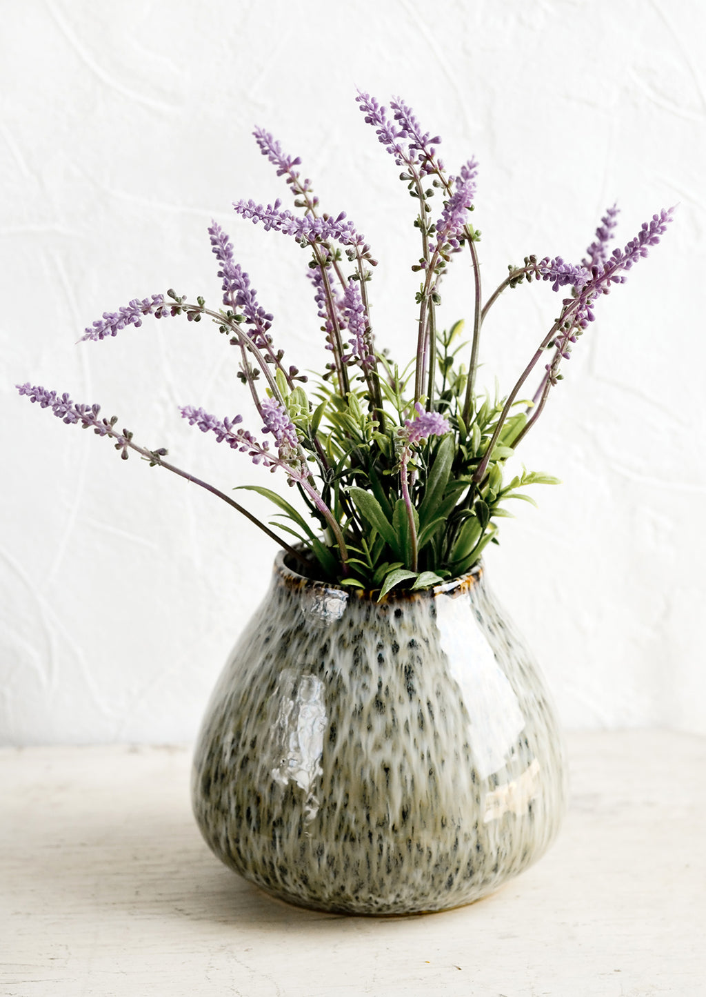 2: A round vase in glossy, speckled green glaze with lavender flowers.