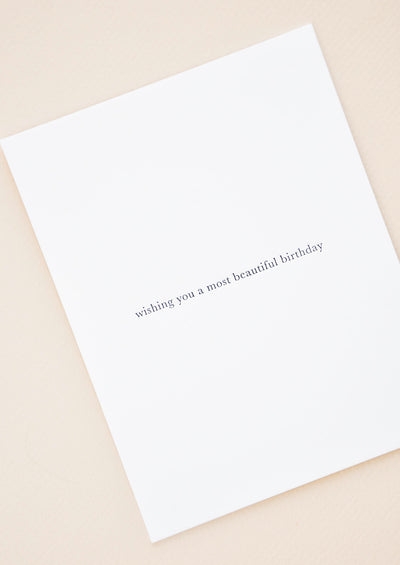 "A simple white greeting card with lowercase text at center reading ""wishing you a most beautiful birthday"" in one line."