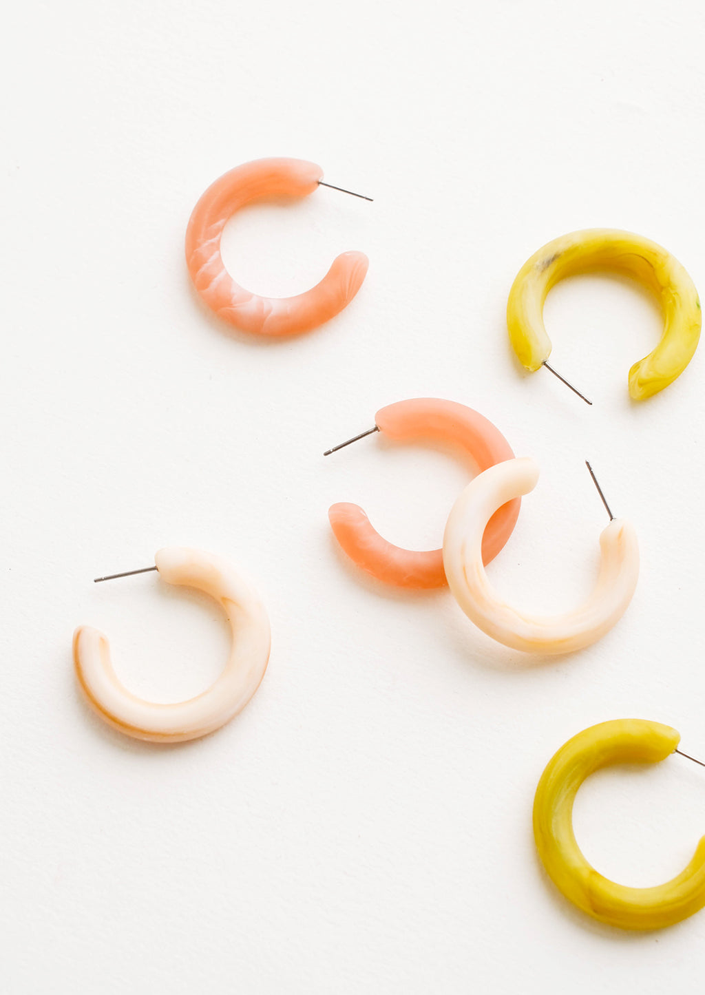 1: Scattered array of different colored hoop earrings in matte resin