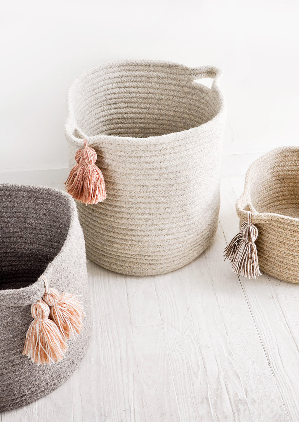 2: Round storage bins in natural wool. Handles at sides with oversized tassel detail.