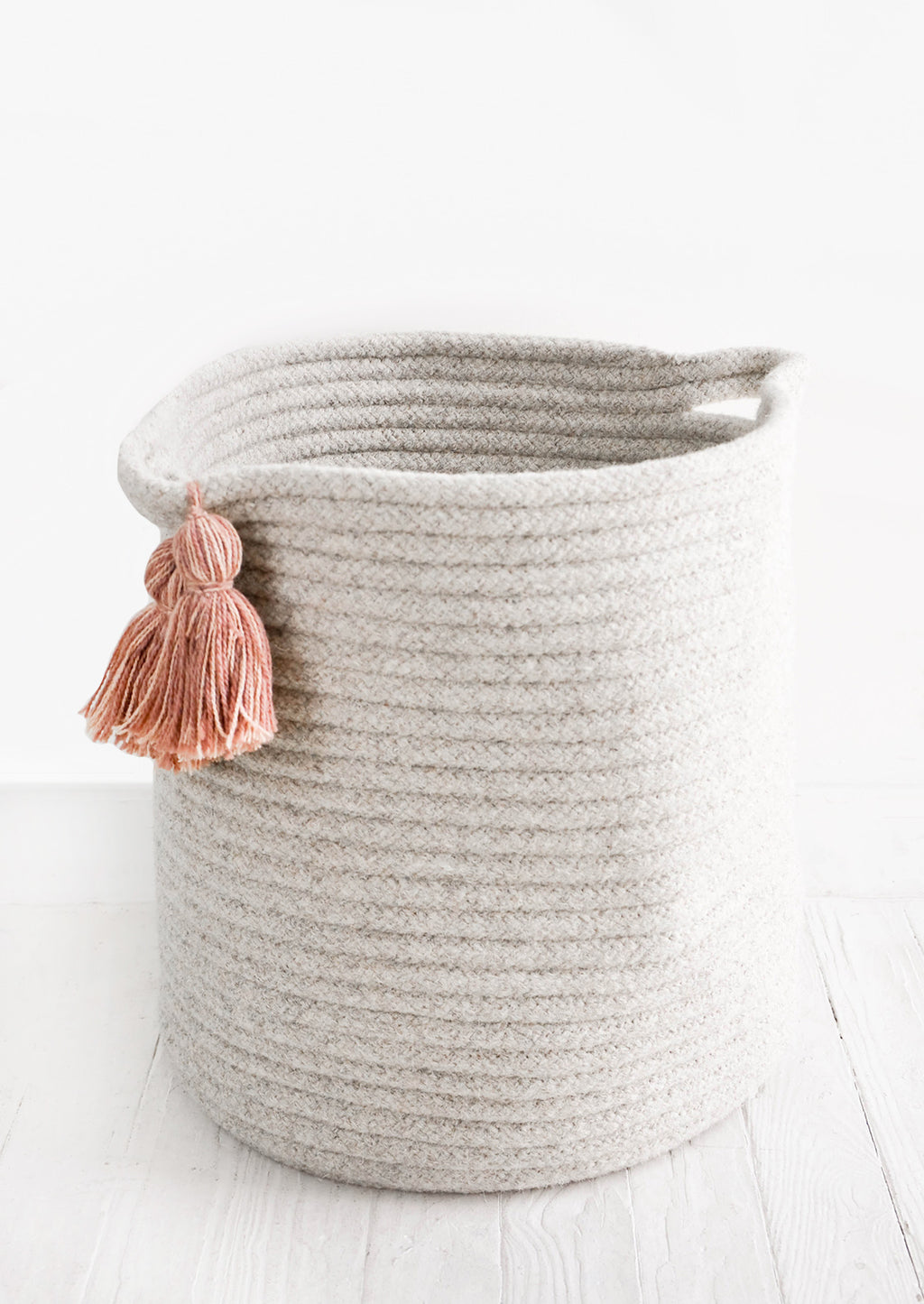 Large / Cream: Round, tall storage bin in natural wool. Handles at sides with oversized tassel detail.