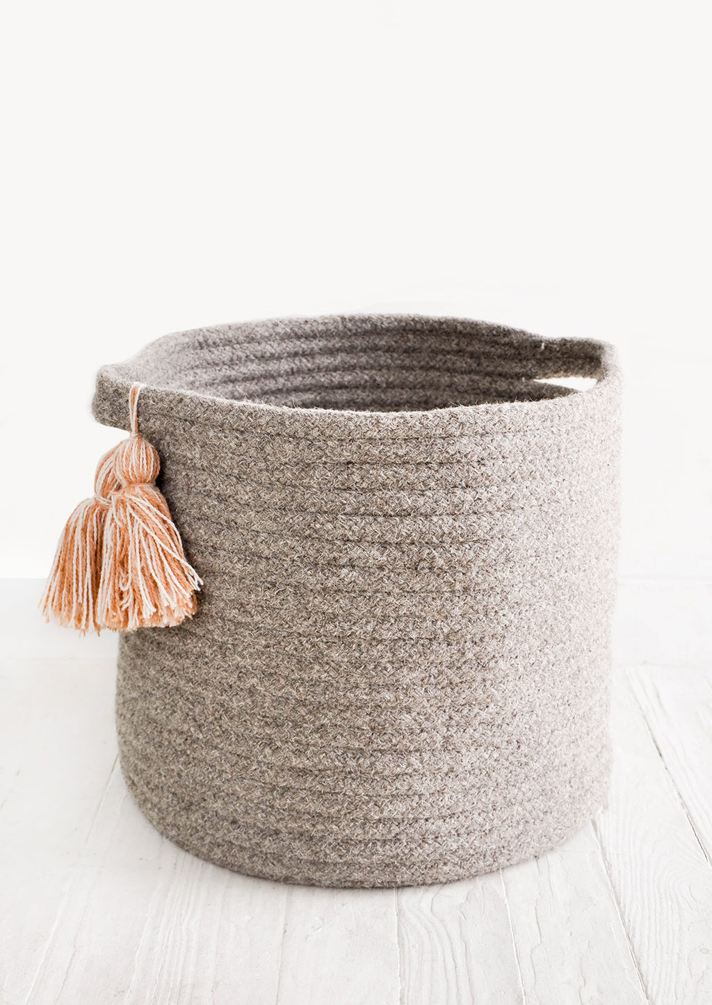 Medium / Taupe: Round, low storage bin in natural wool. Handles at sides with oversized tassel detail.