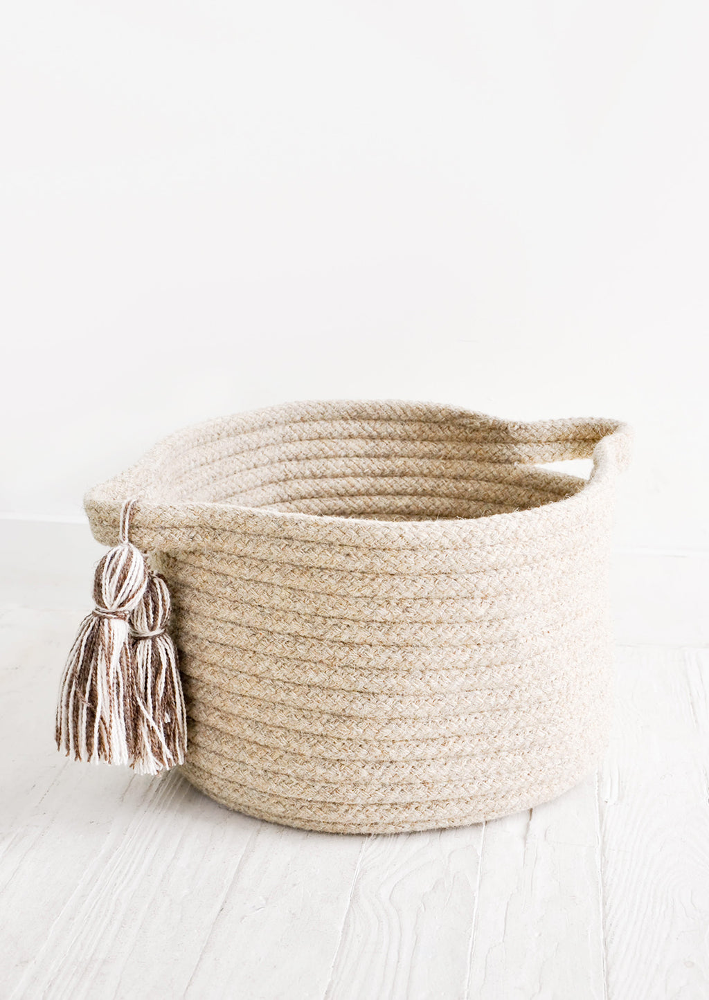 Small / Oatmeal: Round, low storage bin in natural wool. Handles at sides with oversized tassel detail.