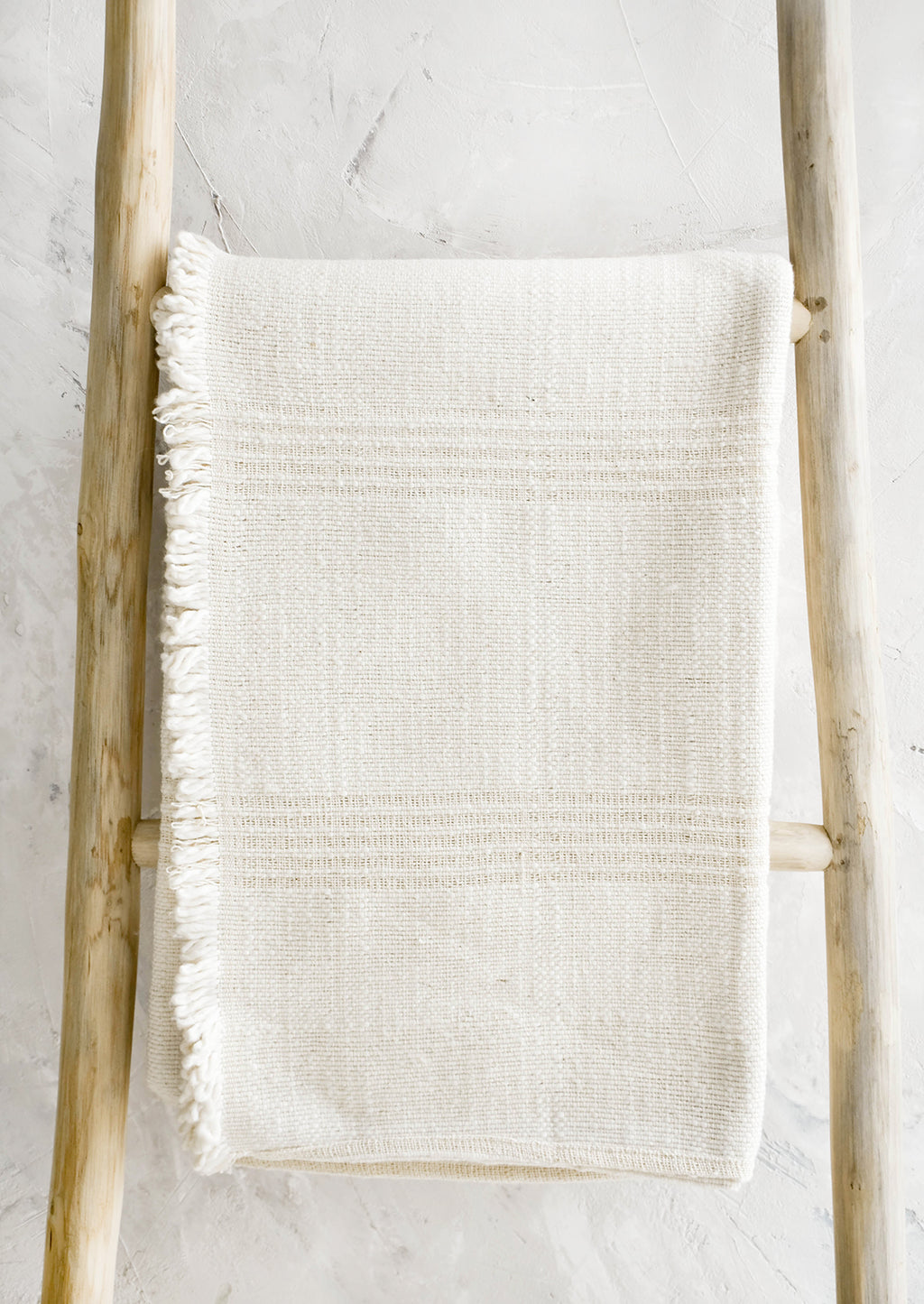 1: Woven throw made from natural undyed cotton with textural tonal stripes and fringed trim on one side