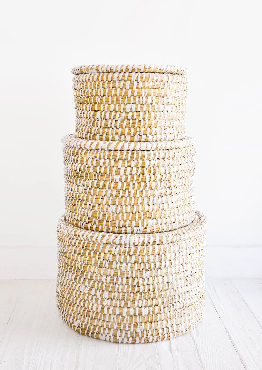 2: Stack of round, lidded storage baskets in three incremental sizes