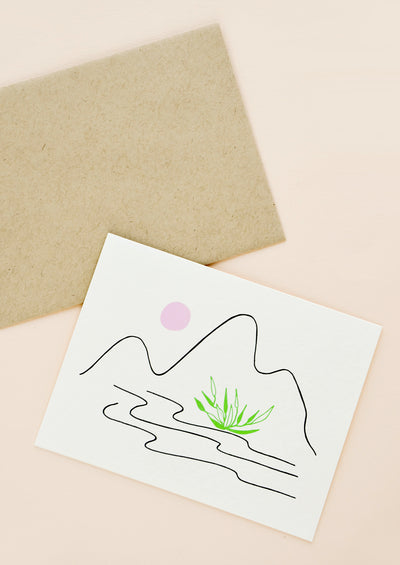 A brown paper envelope and an off white greeting card with a minimalist growing of mountains and a stream in black with a pink sun and a patch of green grass.