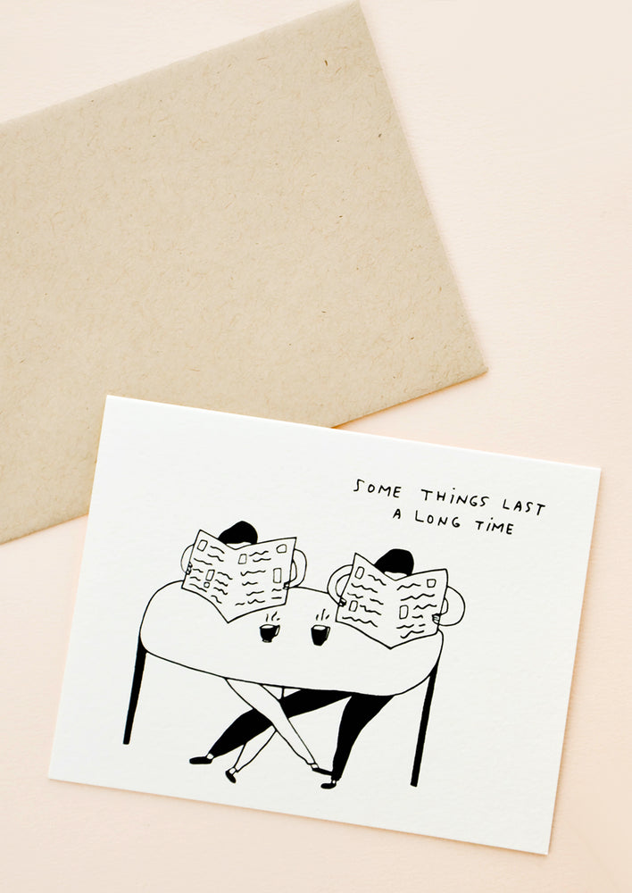 "1: Greeting card with couple sitting at table with coffee cups and both reading newspapers, written text at corner reads ""Some things last a long time"""