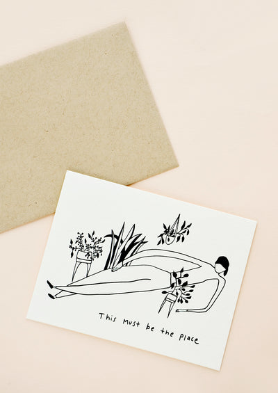 "Greeting card with illustration of woman lying down, surrounded by potted plants, with the text ""this must be the place"" at bottom"