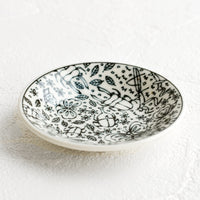 2: A round ceramic trinket dish in black and white with insect print.