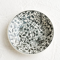 1: A round ceramic trinket dish in black and white with insect print.