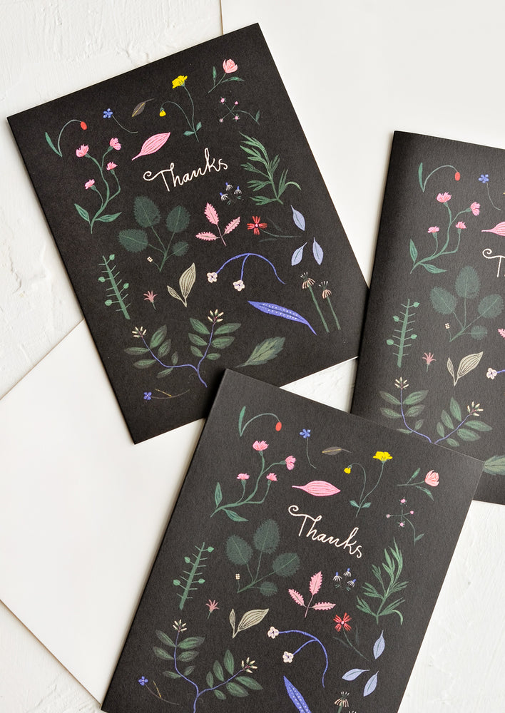 1: Three identical greeting cards in floral print with black background.