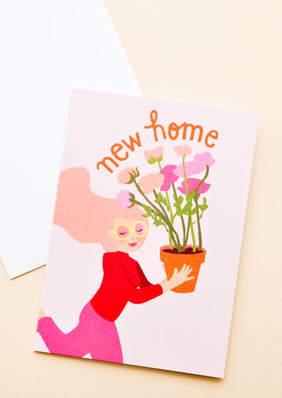 "Pink notecard with drawing of girl holding a Flowerpot and the text ""New Home"", with white envelope."