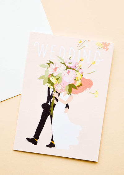 "Pink greeting card with illustration of a bride and groom holding oversized floral bouquet. ""Wedding"" written in white text."