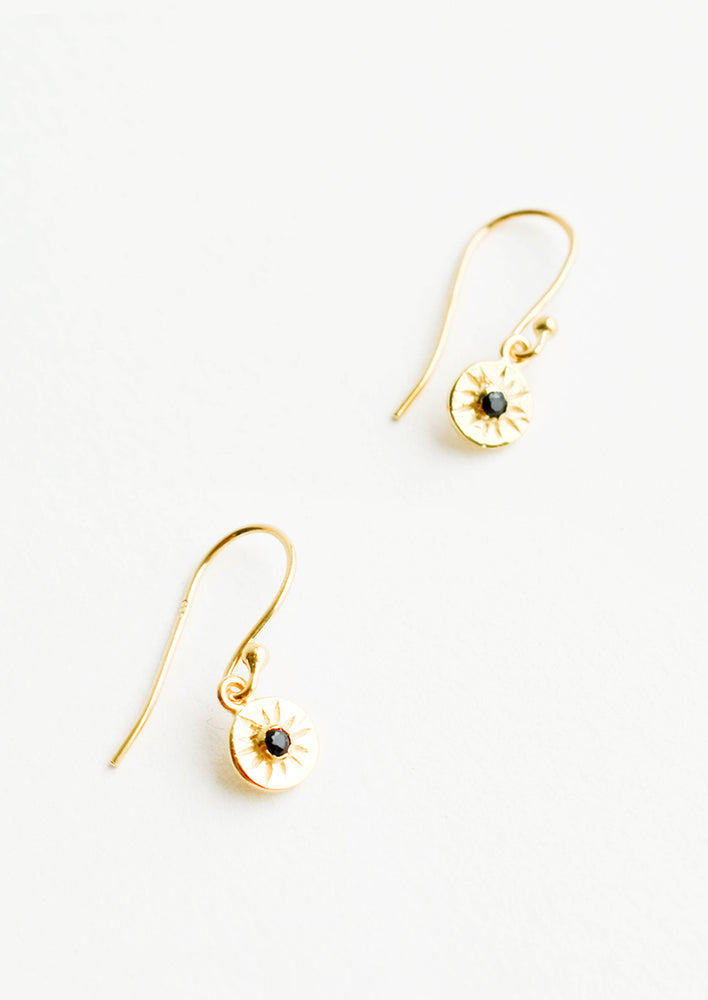 Black Spinel: Dangling gold earrings, hanging from the earring stem is a small gold circular charm with black inset stone and etched decorative lines.