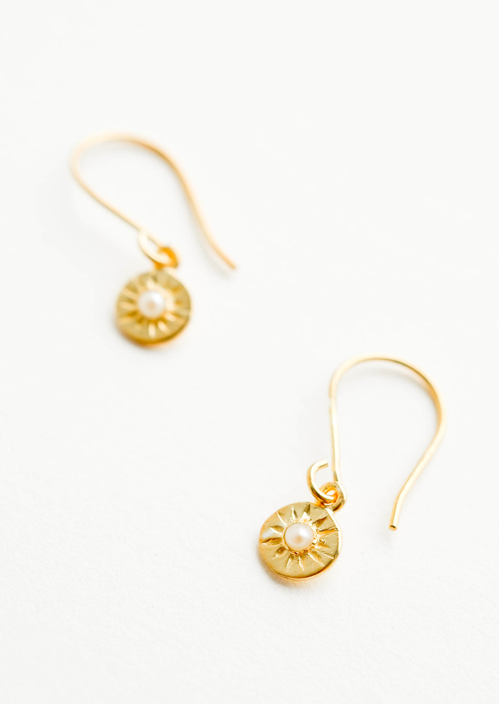 Pearl: Dangling gold earrings, hanging from the earring stem is a small gold circular charm with pearl inset stone and etched decorative lines.