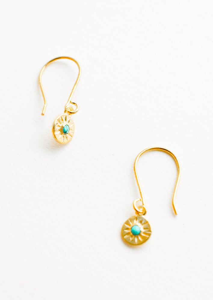 Turquoise: Dangling gold earrings, hanging from the earring stem is a small gold circular charm with turquoise inset stone and etched decorative lines.