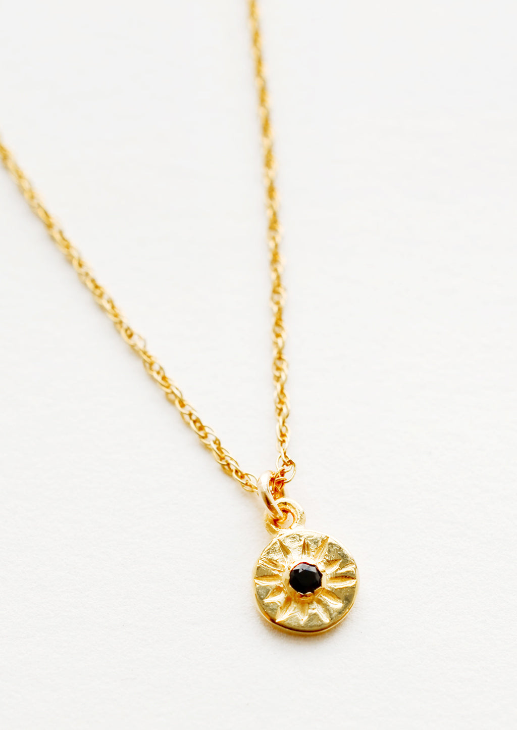 Black Spinel: Detail of necklace with thin gold chain and small golden pendant with black stone at center.