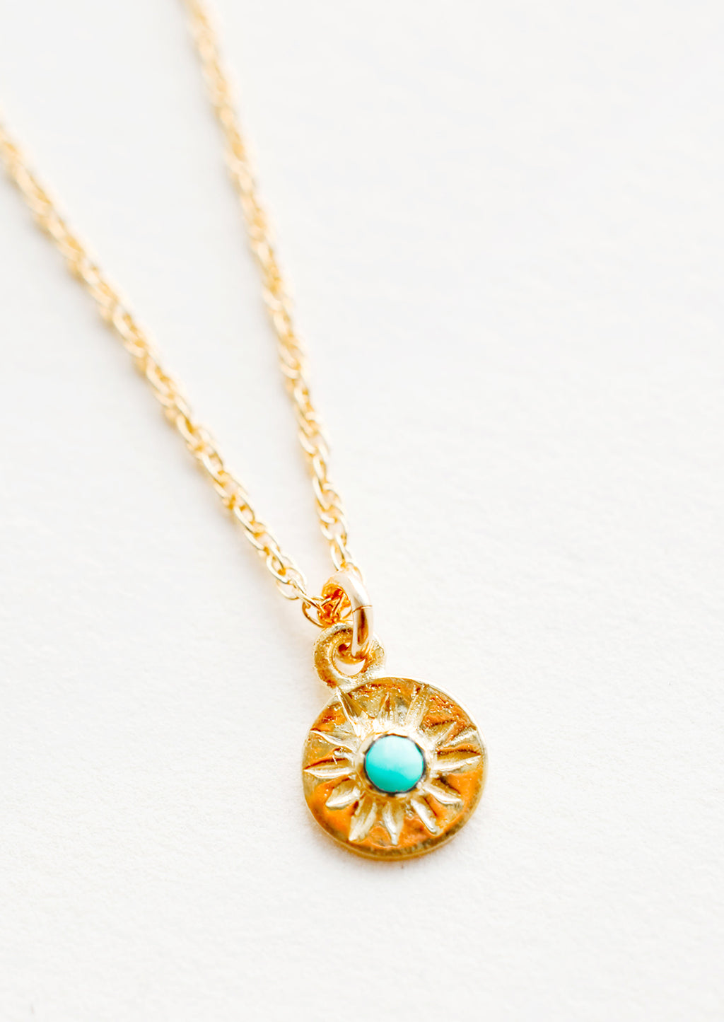 Turquoise: Detail of necklace with thin gold chain and small golden pendant with turquoise stone at center.