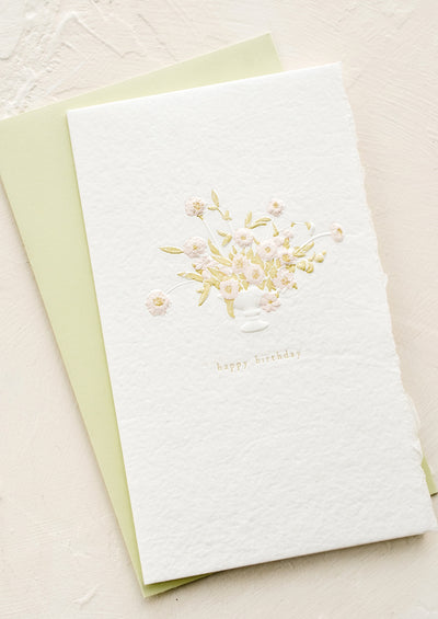 "A greeting card in handmade white paper with floral vase imagery and ""Happy Birthday"" text."