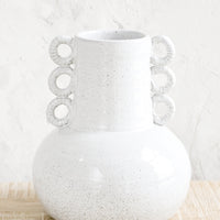 1: Ceramic vase in speckled white glaze. Shape is bulbous at bottom with tapered top and decorative round handles at sides.