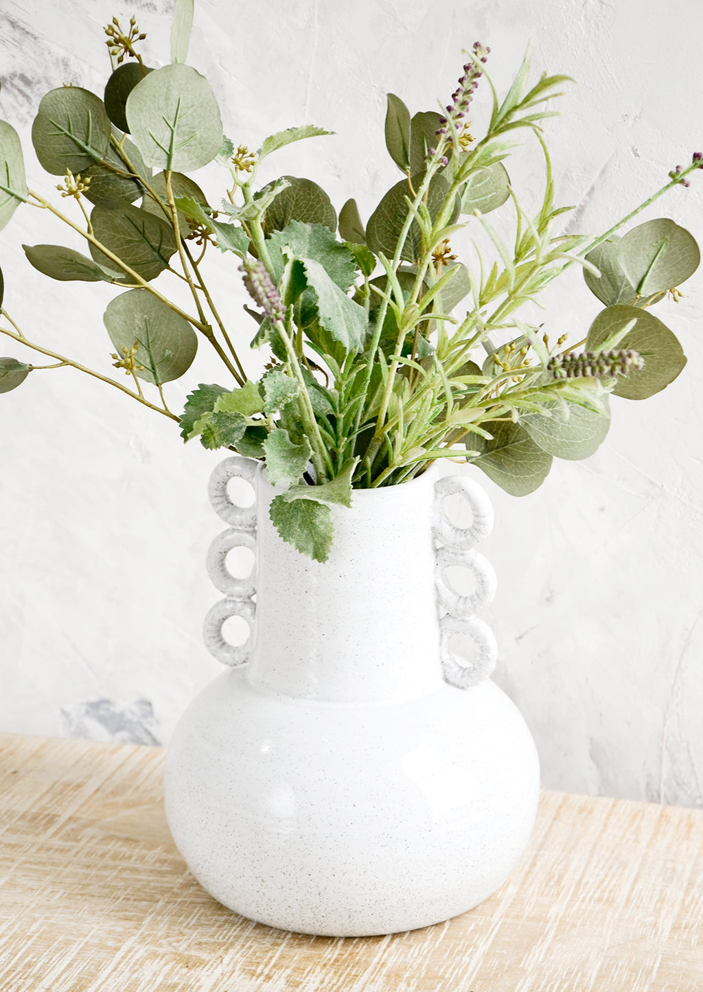 2: Large sculptural white ceramic vase on a rustic table with a mix of herbs & eucalyptus