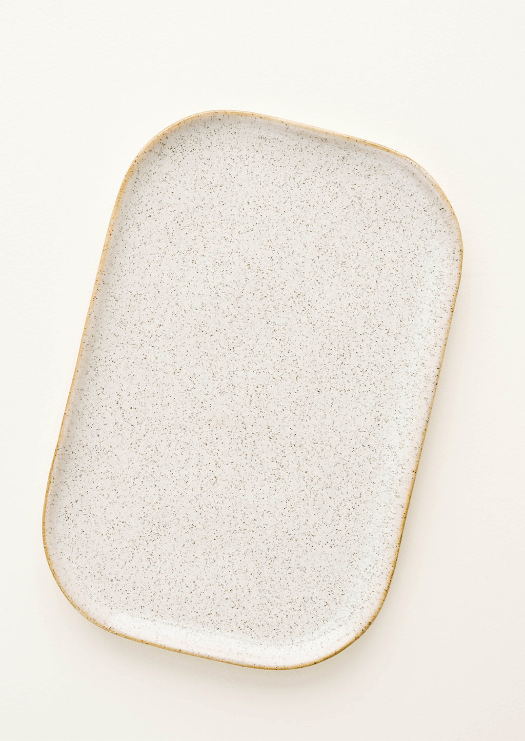 3: Glossy white ceramic tray with brown speckles.