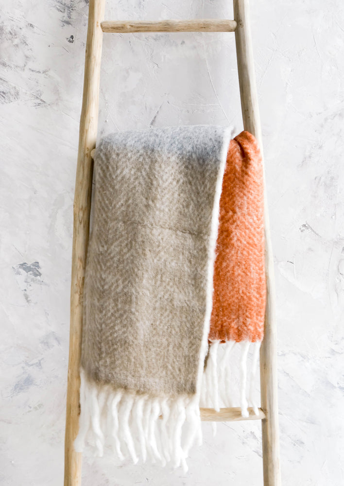 2: Chunky knit throw blanket in tricolor design with chunky white fringe trim, folded over wooden ladder