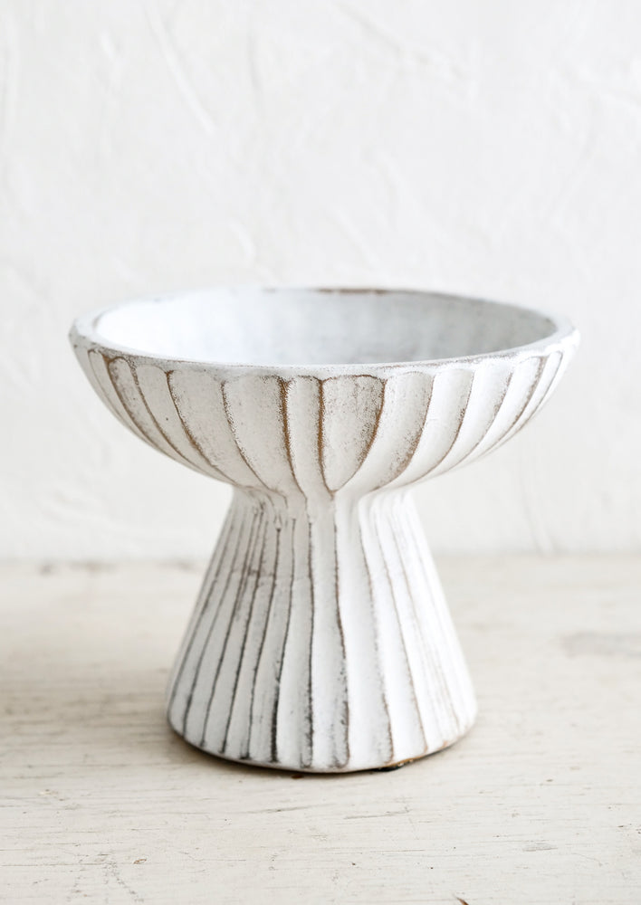 1: A ceramic pedestal bowl in distressed white ceramic with groove texture.
