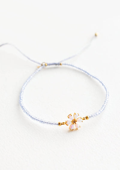 A delicate bracelet of pale blue glass beads and a small iridescent gam flower charm.