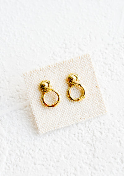 A pair of small brass stud earrings with an organic wabi sabi post and circular bottom.