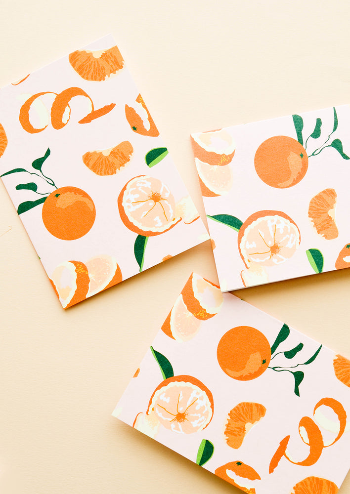 1: Set of cards with pink background and allover orange citrus print