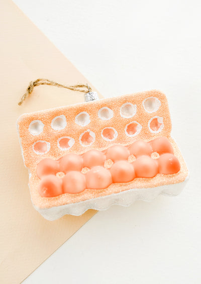 A holiday ornament designed to look like an open carton of a dozen eggs.