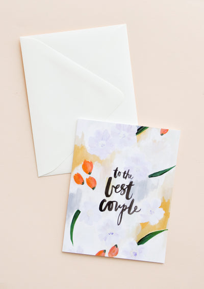 "A white envelope and greeting card featuring a painterly floral scene and the words ""to the best couple"" in black lowercase script."