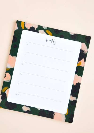 Desktop paper notepad for weekly planning, decorated with painted colors.