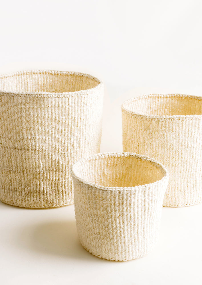 2: Round storage baskets in three incremental sizes made from woven sisal fiber in natural bleached hue