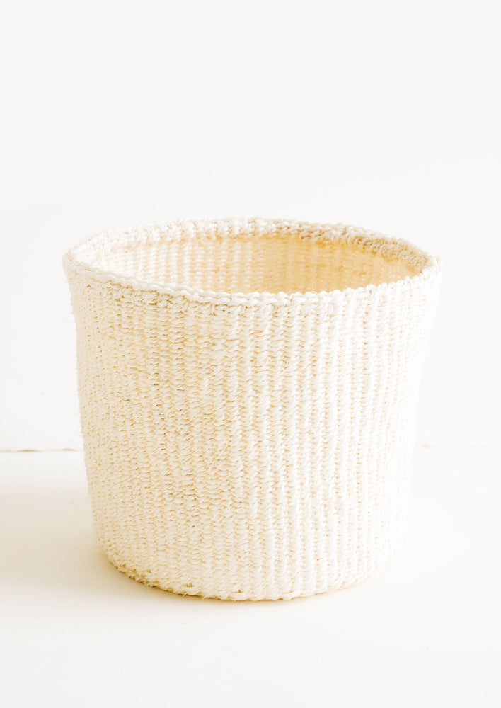 1: Round storage basket made from woven sisal fiber in natural bleached hue