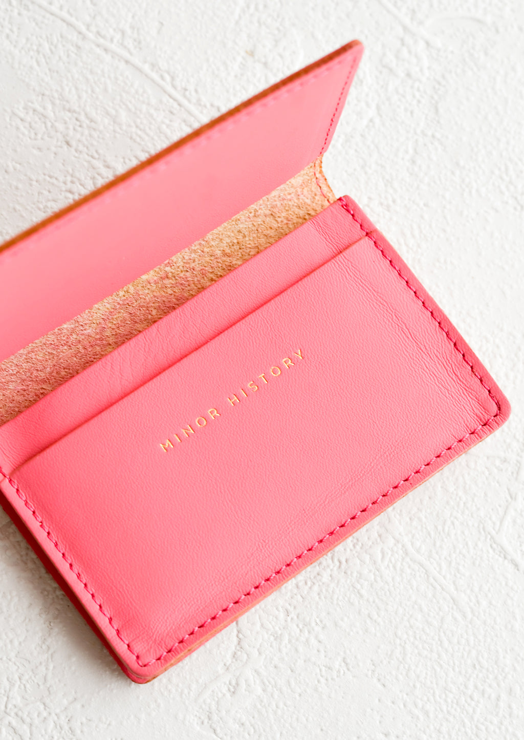 Peony: A bright pink leather card holder wallet with interior sleeve and gold branding.