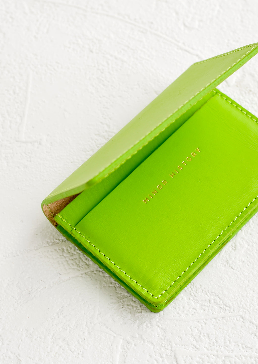 Lime: A lime green leather card holder wallet with interior sleeve and gold branding.