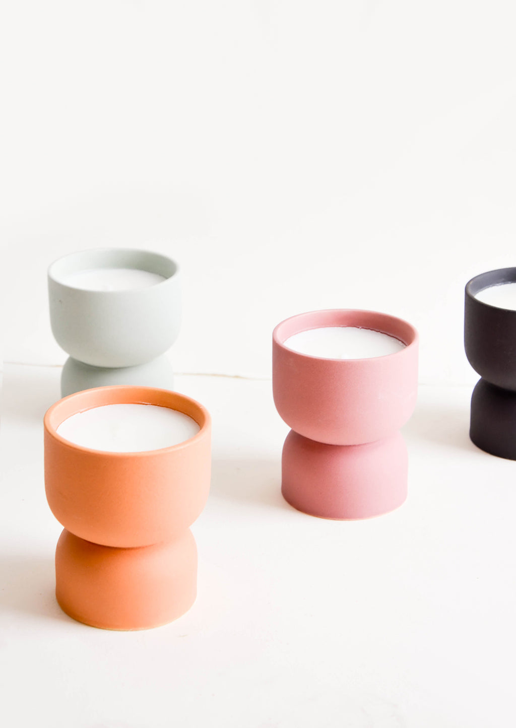 1: Scented candles in hourglass-shaped matte ceramic containers in assorted colors
