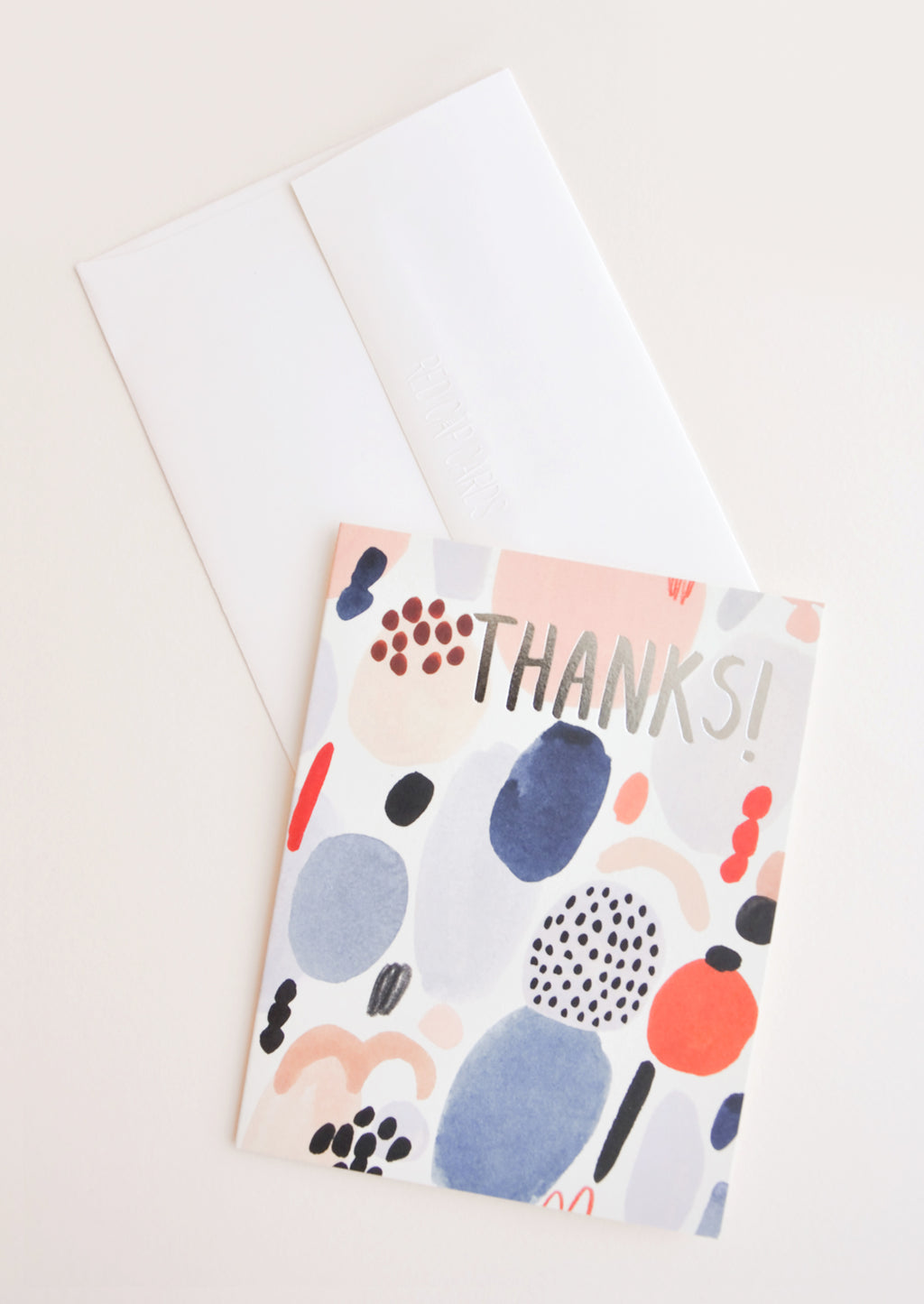 "1: Notecard with colorful abstract shapes and the text ""Thanks!"", with white envelope."