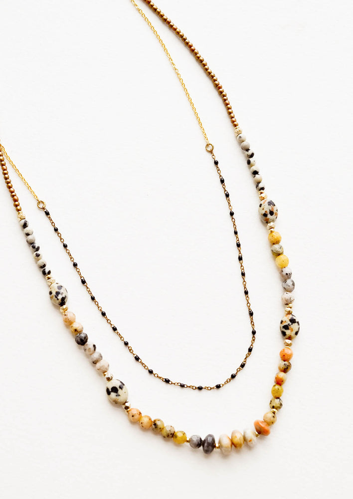 Layered beaded necklace with the shorter strand featuring gold chain alternating with black beads, and the longer chain featuring speckled dalmatian jasper beads.