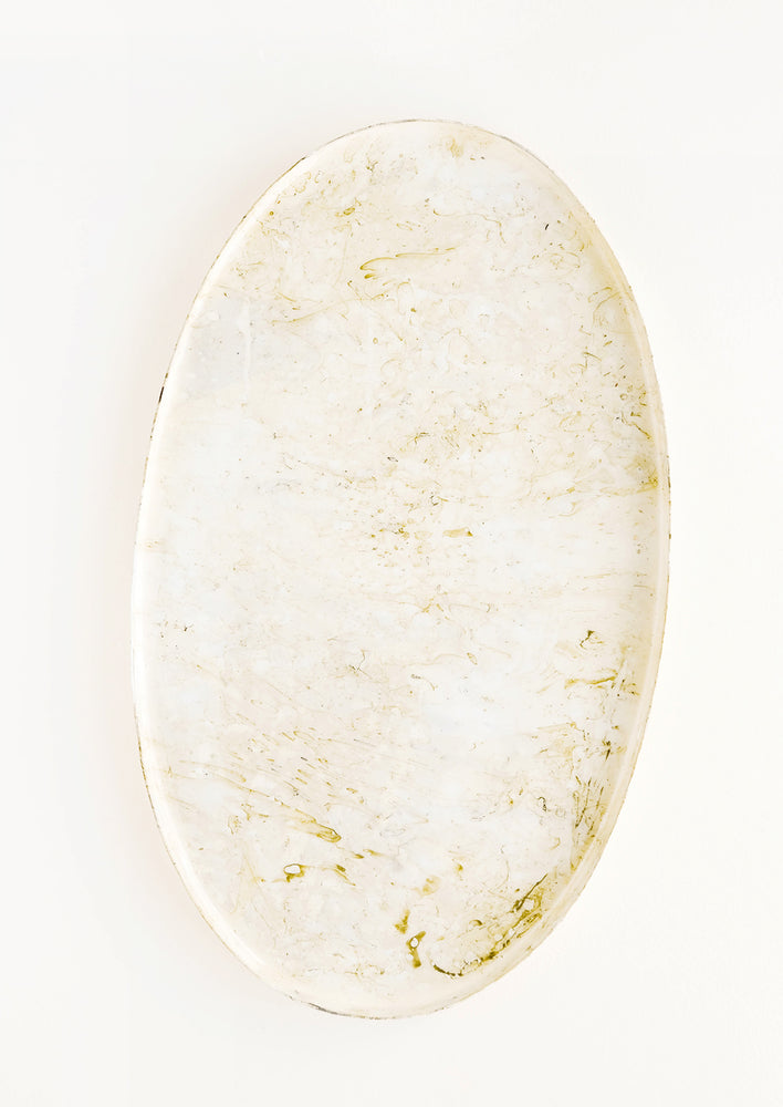 1: Oval shaped decorative tray with lipped rim, covered in a shiny enamel finish in an off-white, marble-like pattern.