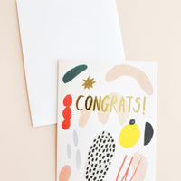 "1: Notecard with colorful abstract shapes and the word ""Congrats"" in gold, and white envelope."