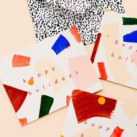 "1: Three matching greeting cards with hand-painted brushstrokes and ""happy holidays"" in red lettering."