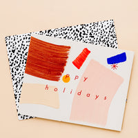 "2: A greeting card with hand-painted brushstrokes and ""happy holidays"" in red lettering, and a black and white patterned envelope."